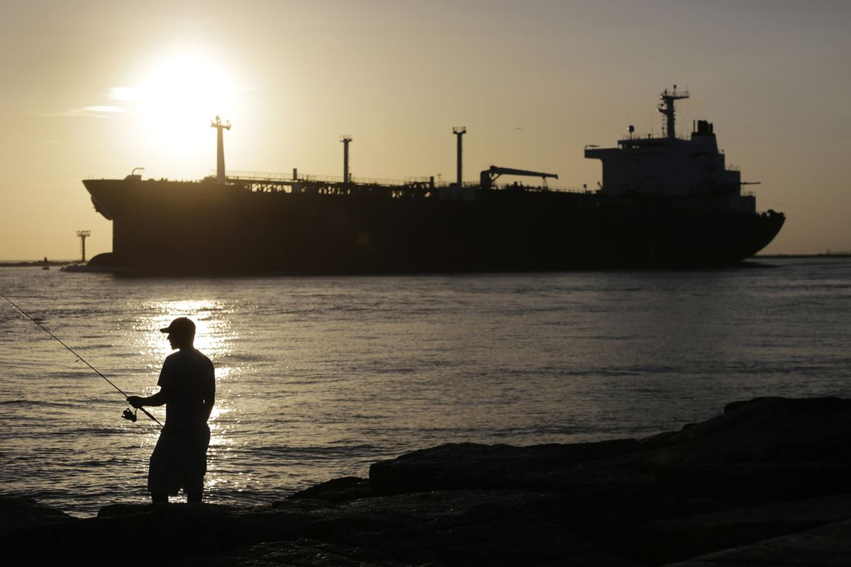 An oil tanker passes a fisherman as it enters a channel near Port Aransas, Texas, heading for the Port of Corpus Christi in this 2015 file photo. Alaska's state treasury is enjoying the benefit of a large spread between the price of Brent crude oil and abundant shale priced to West Texas Intermediate. (Photo/File/AP)