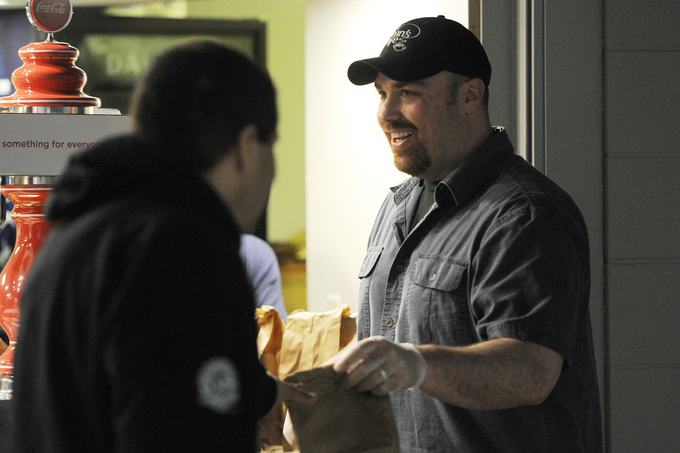 Bean's Cafe food services supervisor Aaron Lochridge distributed sack lunches to clients at the emergency shelter inside the Sullivan Arena during the COVID-19 pandemic on Wednesday, April 29, 2020. (Bill Roth / ADN)