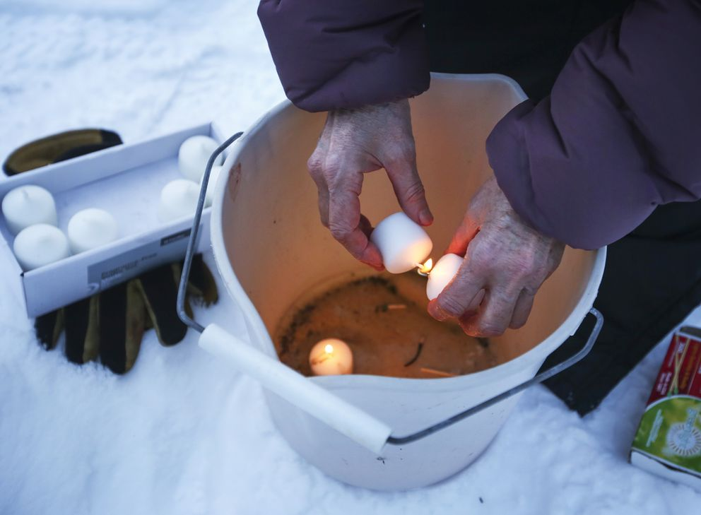Colette Ravinet lights candles to place in her ice luminarias as it begins to get dark in Anchorage on Wednesday. (Emily Mesner / ADN)