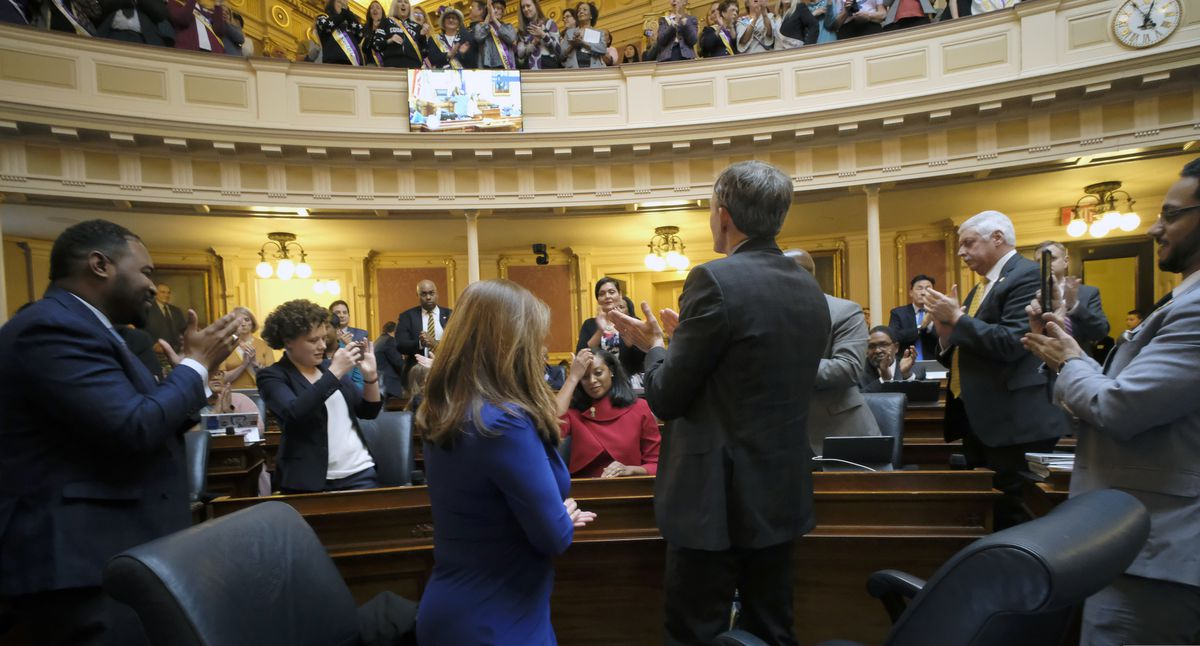 Del. Jennifer Caroll Foy, D-Prince William, seated, center, is applauded by fellow members and ERA suporters in the House of Delegates gallery after she spoke for passage of the ERA resolution she sponsored inside the State Capitol in Richmond, Va., Wednesday, Jan. 15, 2020. (Bob Brown/Richmond Times-Dispatch via AP)