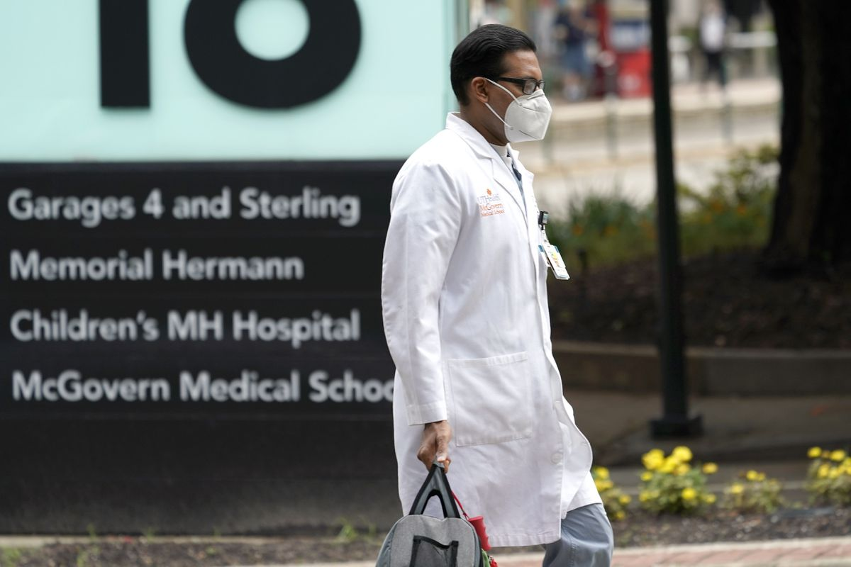 A healthcare professional walks through the Texas Medical Center Thursday, June 25, 2020, in Houston. The leaders of several Houston hospitals said they were opening new beds to accommodate an expected influx of patients with COVID-19, as coronavirus cases surge in the city and across the South. (AP Photo/David J. Phillip)