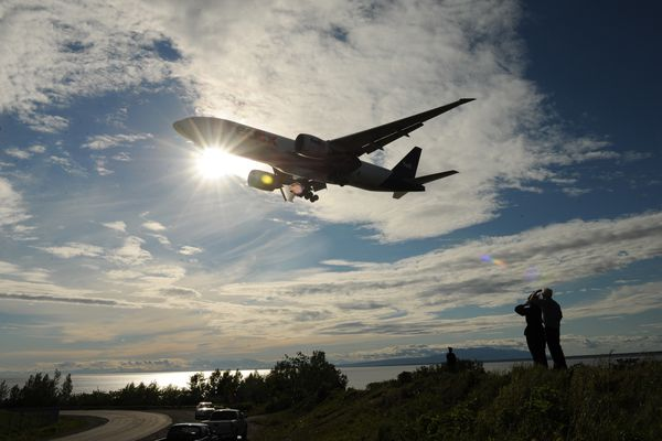 Joan Paal-Fridley and David Fridley, from Big Lake, watch a FedEX Jet plane make a landing approach at Ted Stevens Anchorage International Airport on Thursday, June 14, 2012. (Bob Hallinen / Alaska Dispatch News)