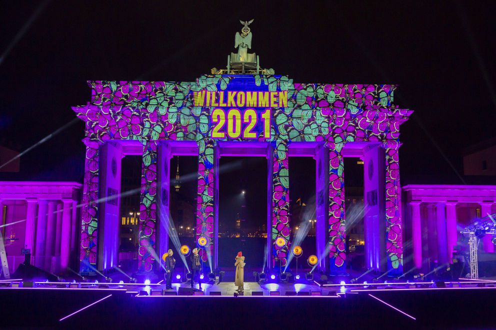 'Welcome 2021 ' is projected onto the Brandenburg Gate in Berlin on Thursday, Dec. 31, 2020. The New Year's Eve party at the historic landmark has been cancelled due to coronavirus pandemic. (Christoph Soeder/dpa via AP)