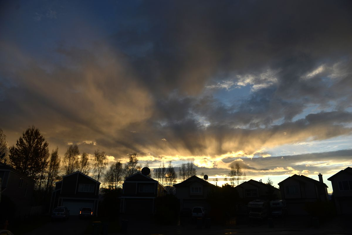 Crepuscular rays fan out over a west Anchorage, AK neighborhood just after sunrise on Tuesday, Oct 15, 2018. (Bob Hallinen / ADN)