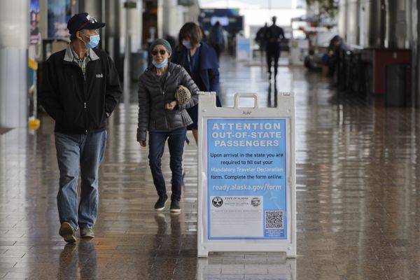 A sign gives travelers from out-of-state instructions to fill out a declaration online at Ted Stevens Anchorage International Airport on May 11, 2020. (Marc Lester / ADN)
