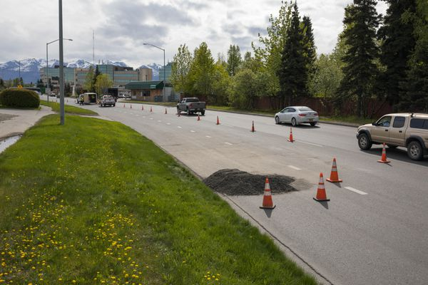 A sinkhole is filled with recycled asphalt Friday, May 25, 2018 on Benson Blvd. The Alaska Department of Transportation still needs to determine what caused the 15-foot deep hole to open up before a permanent fix can be applied. (Loren Holmes / ADN)