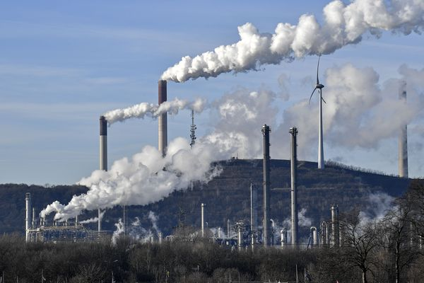 FILE-In this Jan. 16, 2020 file photo an uniper coal-fired power plant and BP refinery steam beside a wind generator in Gelsenkirchen, Germany. The state governors Dietmar Woidke of Brandenburg, Michael Kretschmer of Saxony, Reiner Haseloff of Saxony-Anhalt and Armin Laschet of North Rhine-Westphalia meet in Berlin for the adoption by the Bundestag and Bundesrat of the laws on coal phase-out and structural strengthening in the affected federal states. (AP Photo/Martin Meissner)