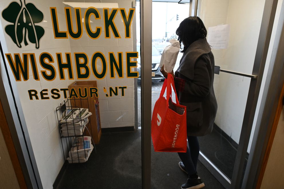 DoorDash 'Dasher ' Johnise Morning picks up an order for a customer at the Lucky Wishbone on Tuesday, March 17, 2020. On Monday, Anchorage Mayor Ethan Berkowitz issued an order prohibiting dine-in service for food and drinks through March 31. (Bill Roth / ADN)