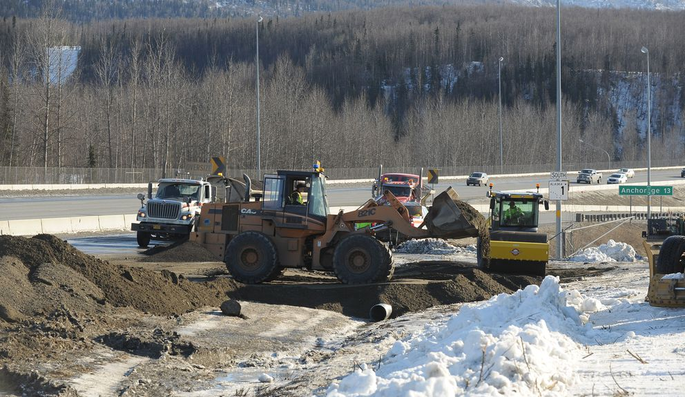 Alaska Department of Transportation workers create a new entrance to the Glenn Highway just past the damaged South Eagle River overpass on Thursday afternoon.  (Bob Hallinen / ADN)