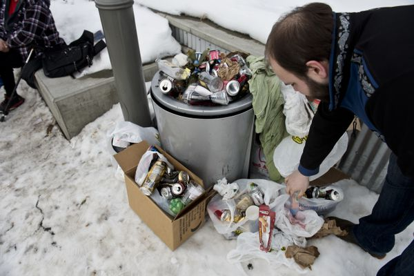 Daniel George, treasurer of Mountain View Community Council, looks at a pile of mostly empty alcohol containers along Mountain View Drive and North Bragaw Street on March 15, 2018. The Mountain View Community Council is working with Brown Jug Liquor Store on North Bragaw Street to address alcohol-related concerns along Mountain View Drive. (Marc Lester / ADN)