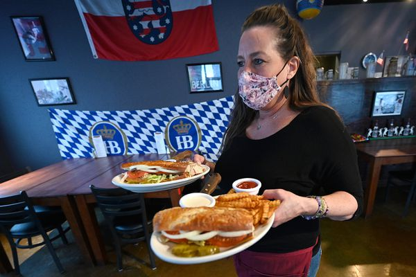 Server Hollie Mitchell brings a Rinderbrust Roll order to a table at the West Berlin restaurant in Mt. View on Tuesday, Jan. 12, 2021. (Bill Roth / ADN)
