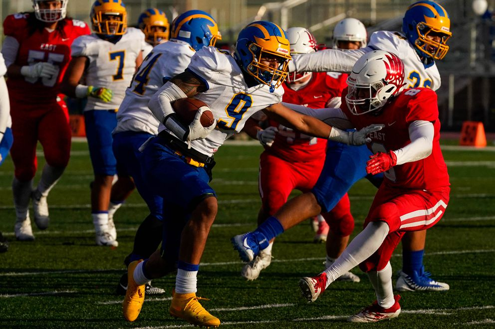 Bartlett's Elijah Lewis-Tufi tries to push past on East player in a Sept. 25 meeting won by East, 14-8. (Loren Holmes / ADN)
