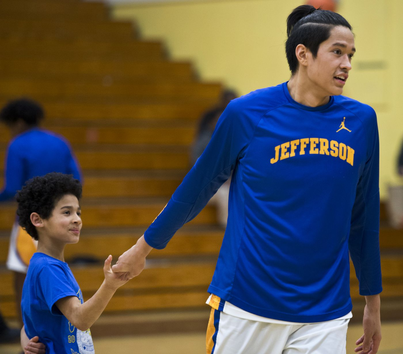 Jefferson High School ball boy Brave Johnson slaps hands with Kamaka Hepa before a game on Feb. 13, 2018, in Portland, Oregon. (Marc Lester / ADN)