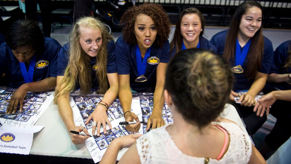 Members of UAA's women's basketball team talk with a young fan. (Marc Lester / ADN archive)