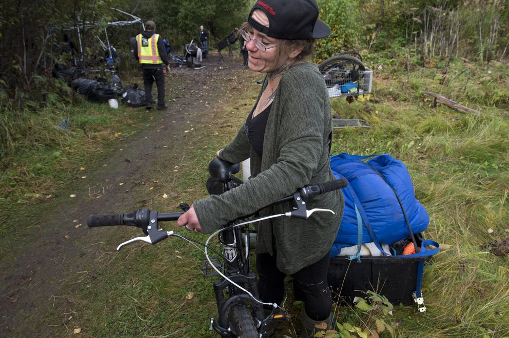 Toni Anaruk removes items from a camp near Spenard Road on September 21, 2018. City officials began a pilot program to clean up homeless camps in three days, while allowing evicted campers to store their belongings for 30 days at Central Transfer Station. (Marc Lester / ADN)