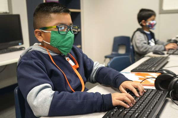 FILE - In this Dec. 3, 2020, file photo, students wearing face masks work on computers at Tibbals Elementary School in Murphy, Texas. A new poll from The University of Chicago Harris School of Public Policy and The Associated Press-NORC Center for Public Affairs Research finds that most parents fear that their children are falling behind in school while at home during the pandemic (AP Photo/LM Otero, File)
