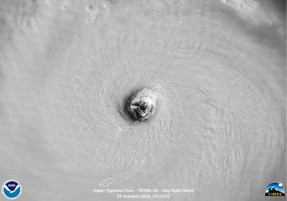 This satellite image provided by the National Oceanic and Atmospheric Administration (NOAA) shows the moment the eye of Super Typhoon Yutu passed directly over Tinian Island, one of three main islands of the U.S. Commonwealth of the Northern Mariana Islands, producing damaging winds and high surf Wednesday, Oct. 24, 2018. The National Weather Service in Honolulu says maximum sustained winds of 180 mph (290 kph) were recorded around the eye of the storm, which passed over Tinian island and Saipan early Thursday morning local time. Waves of 25 to 40 feet (6 to 12 meters) are expected around the eye of the storm. (NOAA via AP)
