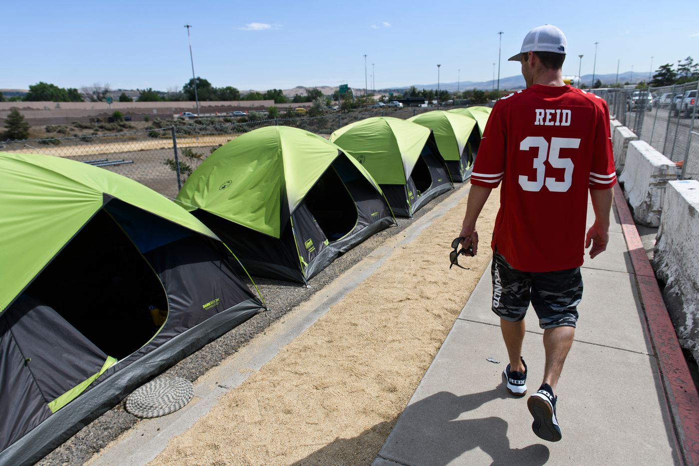 Courtney Govan walks to his tent at a new sanctioned tent camping site a few blocks from the Nevada CARES Campus on June 24, 2021. He said he prefers it to the large shelter. 'I get my own privacy. I can shut my door, ' he said. (Marc Lester / ADN)