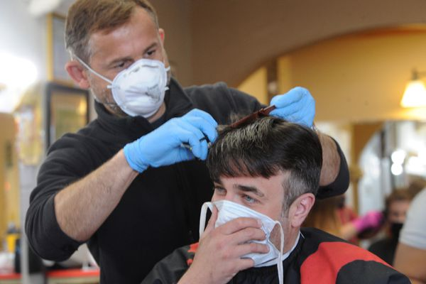 Steven Cehula wears a mask as barber Brian Lena cuts his hair at Northern Lights Barber Shop on Monday, April 27, 2020, as businesses began to reopen during the coronavirus pandemic. Cehula said he tried cutting his own hair and