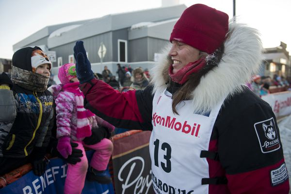 Aliy Zirkle gives young fans a high-five after arriving in Nome on Tuesday in third place in the Iditarod Trail Sled Dog Race.