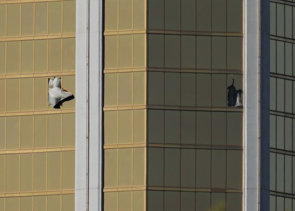 Two broken windows are seen Monday at The Mandalay Bay Resort and Casino following a mass shooting at the Route 91 Harvest Festival in Las Vegas. REUTERS/Mike Blake