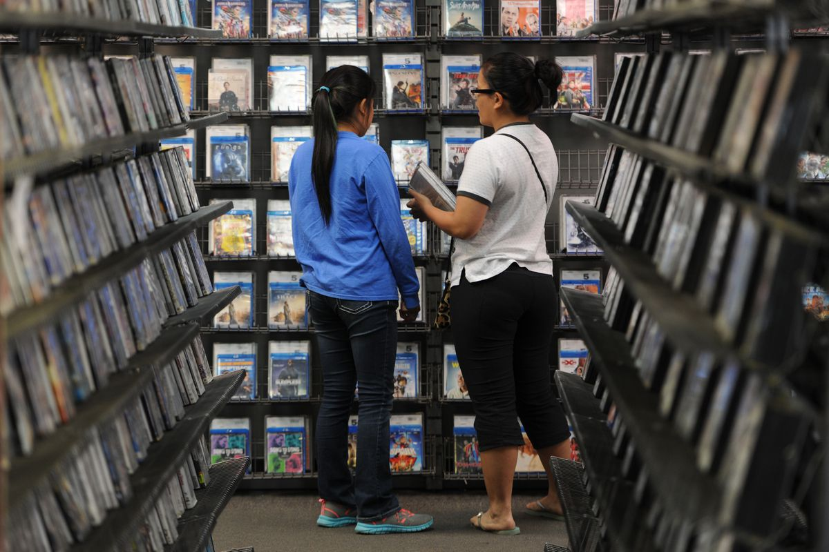 Glaiza Kordus, right, and her 10-year-old daughter Danaiza pick out movies to watch from the Blockbuster store on DeBarr Road on Monday, July 24. (Bill Roth / Alaska Dispatch News)