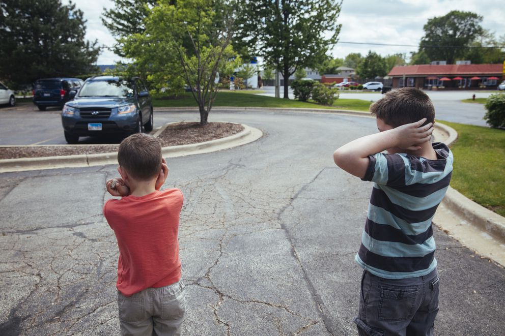 Danielle Rizzo's sons cover their ears as a loud vehicle drives by. Noise sensitivity is a common challenge for people with autism spectrum disorders. (Photo by Taylor Glascock for The Washington Post)