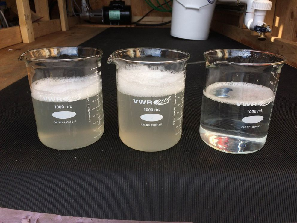 Two beakers with untreated water on the left and a beaker on the right with treated water sit in the lab at UAA in August of 2016. This photograph was taken after bubbles had infiltrated the team's system. (Photo by Kaitlin Mattos)