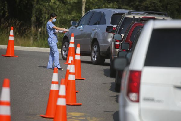 A woman gathers information from a person inside a vehicle who is in line at Walgreens, on the corner of Lake Otis Parkway and E Tudor Road, for covid-19 testing in Anchorage on July 28, 2020. (Emily Mesner / ADN)