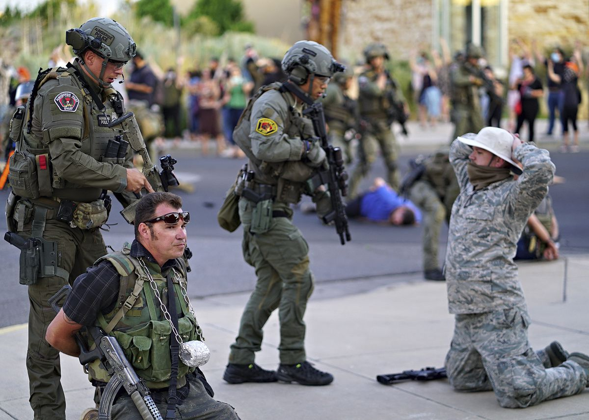 "Albuquerque police detain members of the New Mexico Civil Guard, an armed civilian group, following the shooting of a man during a protest over a statue of Spanish conquerer Juan de Oñate on Monday, June 15, 2020, in Albuquerque, N.M. A confrontation erupted between protesters and a group of armed men who were trying to protect the statue before protesters wrapped a chain around it and began tugging on it while chanting: ""Tear it down."" One protester repeatedly swung a pickax at the base of the statue. Moments later a few gunshots could be heard down the street and people started yelling that someone had been shot. (Adolphe Pierre-Louis/The Albuquerque Journal via AP)"