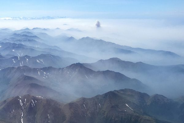 Wildfire smoke hovers around the mountains on the Kenai Peninsula last week, as seen from a plane on its approach to Anchorage on July 3, 2019. (Photo by Alli Harvey)