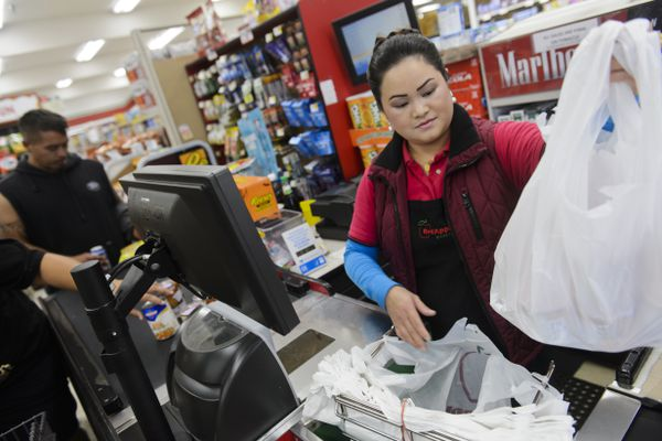 Serena Moua bags items for a Red Apple Markets customer on Bragaw Street on September 10, 2019. Anchorage stores will no longer be permitted to provide plastic bags to shoppers beginning September 15. (Marc Lester / ADN)
