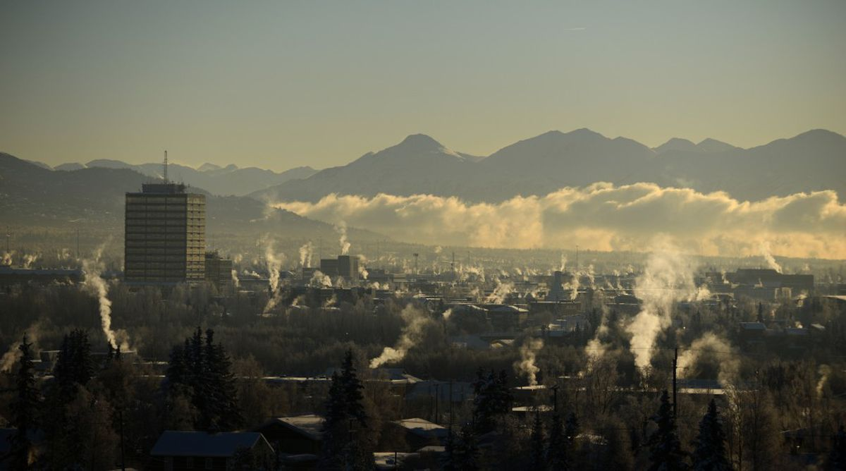 A low cloud bank stretches into Turnagain Arm as steam rises from buildings on a cold morning in Anchorage on Wednesday, January 18, 2017. The Chugach and Kenai mountains form a backdrop for the chilly scene. (Bob Hallinen / Alaska Dispatch News)