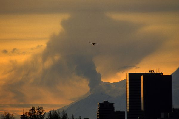 A small airplane banks for Merrill Field as a plume of ash and steam from Mt. Spurr dominates the skyline October 2, 1992. Though the mountain remained on red alert for days, a predicted eruption never materialized. (Paul Souders / ADN archive 1992)
