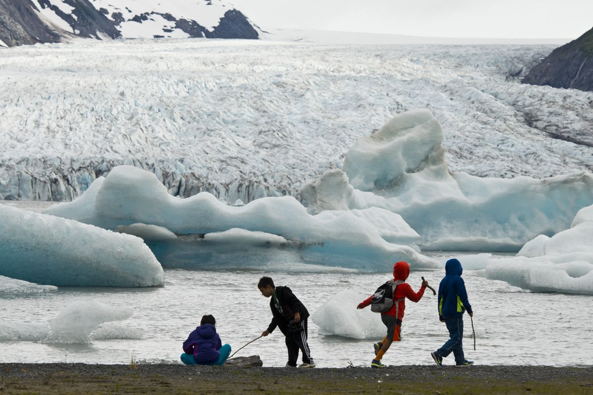 Kids explore the waterline at Spencer Lake with a good view of Spencer Glacier and some of its icebergs on Saturday, June 11, 2016. Hikers can access the area, south of Portage in Chugach National Forest, by way of Alaska Railroad's whistle stop service, which drops passengers about a 1.3-mile walk from the lake. (Marc Lester / ADN archive 2016)