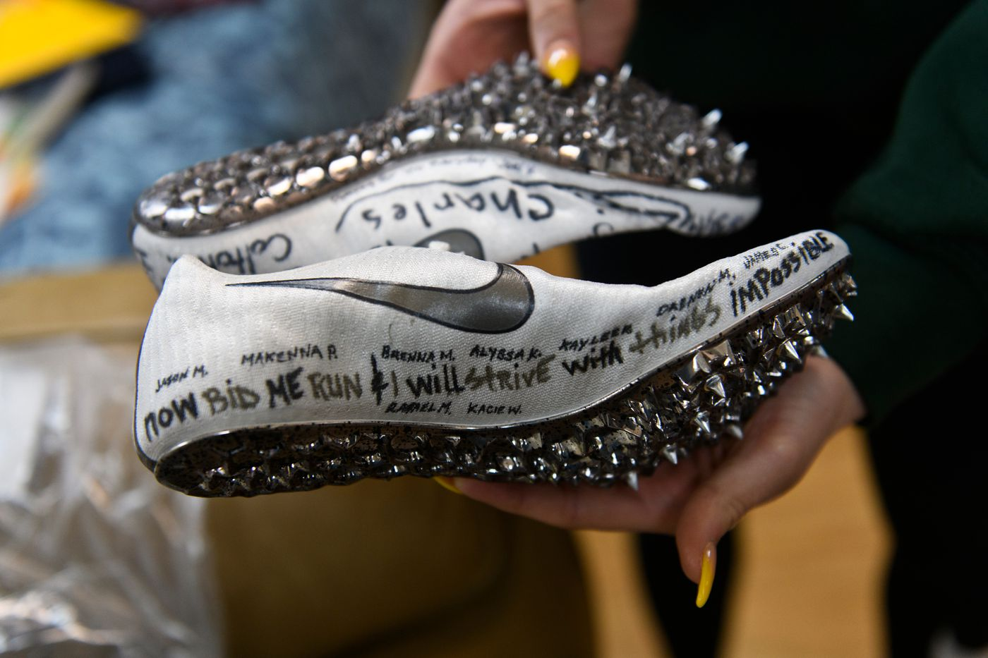 Hailey Williams holds the spikes she had been saving to use during the spring track season this year, which was canceled. On the shoes are written the names of former teammates and other close friends, and a quote from Shakespeare. (Marc Lester / ADN)