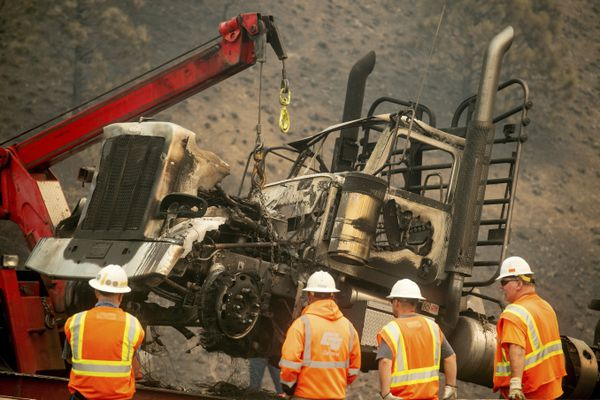 A crane lifts a truck scorched by the Delta Fire on Interstate 5 in the Shasta-Trinity National Forest, Calif., on Thursday, Sept. 6, 2018. The highway remains closed to traffic in both directions as crews battle the blaze. (AP Photo/Noah Berger)