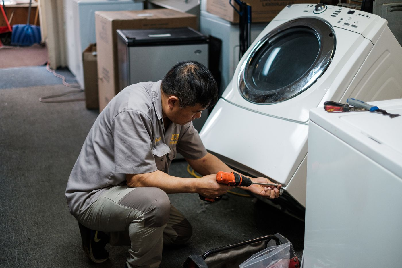Chun B. Park starts to remove the exterior of a dryer unit so that he can start replacing faulty parts. Park spends the first few hours of his work day repairing things in his shop before making house calls. (Young Kim / Alaska Dispatch News)