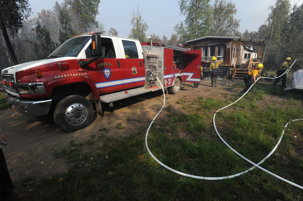 Firefighters mop up hot spots at a residence along the Parks Highway on Tuesday, Aug. 20, 2019. (Bill Roth / ADN)