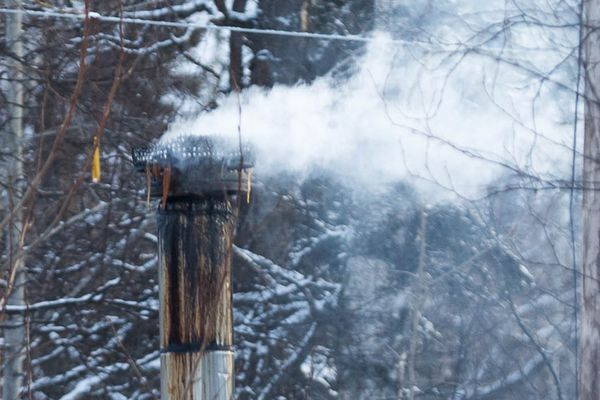 Wood smoke comes out of a chimney at a home in Palmer on Tuesday, Jan. 23, 2018. (Loren Holmes / ADN)