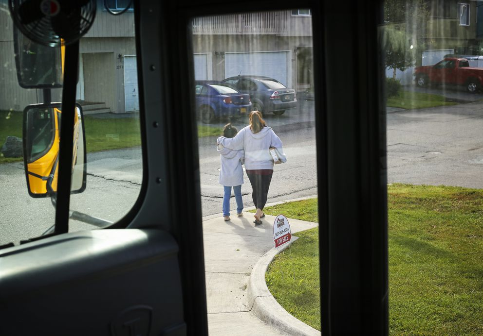 Sidney Riley, left, and Kristine Riley, right, walk back to their home after receiving personal computers, in preparation for the first day of school in Anchorage, on Aug. 19, 2020. (Emily Mesner / ADN)