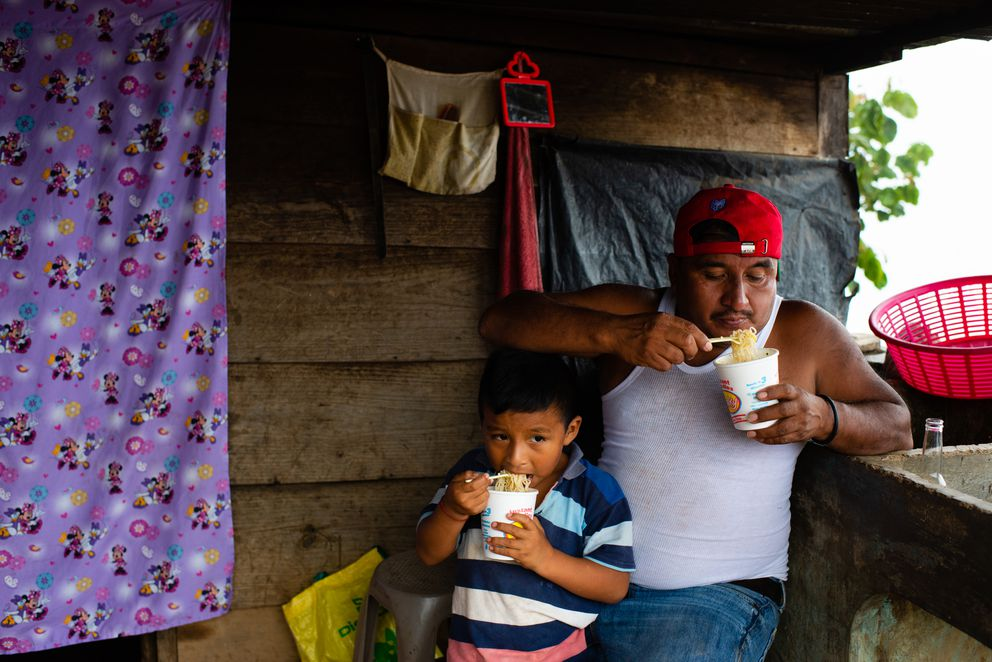 Marvel Carrillo, 5, left, and his father, Rodrigo Carrillo Ordoñez, 48, eat instant noodles outside their small home in Guatemala. (Washington Post photo by Sarah L. Voisin)