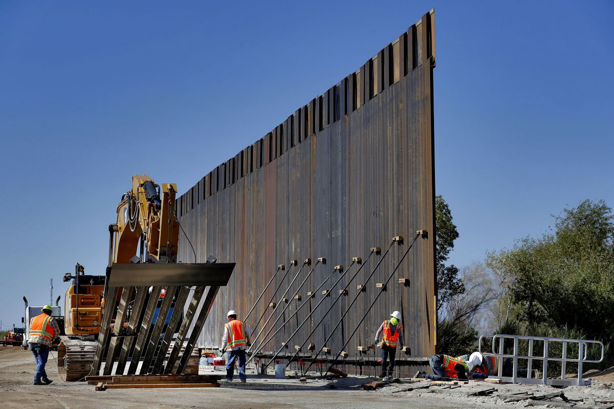 Government contractors erect a section of Pentagon-funded border wall along the Colorado River, Tuesday, Sept. 10, 2019 in Yuma, Ariz. (AP Photo/Matt York)