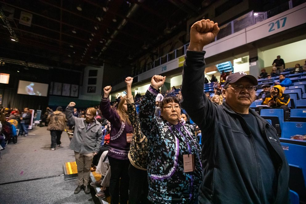 "Chuathbluk residents William Hunter and Teresa Simeon-Hunter stand in silent protest during an address by Alaska Governor Mike Dunleavy during the Alaska Federation of Natives convention Thursday, Oct. 17, 2019 at the Carlson Center in Fairbanks. ""I was only thinking of our kids and our elders, ' said Simeon-Hunter. 'He's cutting funding for schools."" 'He shouldn't be doing that, ' said Hunter. (Loren Holmes / ADN)"