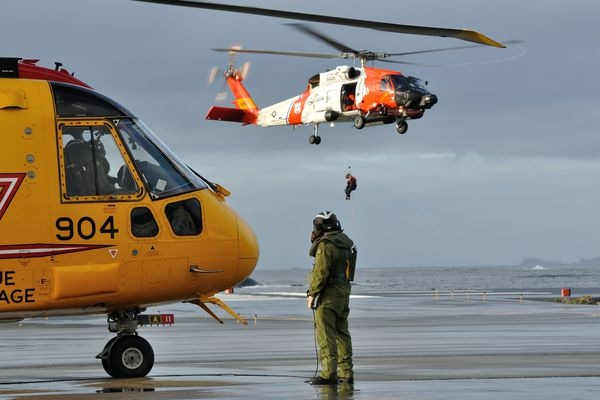 Sgt. Murray Slack, a flight engineer with 442 Transport and Rescue Squadron, Royal Canadian Air Force, conducts pre-start procedure on a Cormorant helicopter at United States Coast Guard (USCG) Air Station Sitka, Alaska, on Oct. 29, 2013, as a USCG H-60 helicopter crew conducts hoist exercises. The 442 Squadron crew was stopping over in Sitka on their way to a joint Canada/U.S. Arctic Search and Rescue Exercise (SAREX) at Joint Base Elmendorf-Richardson, Alaska.