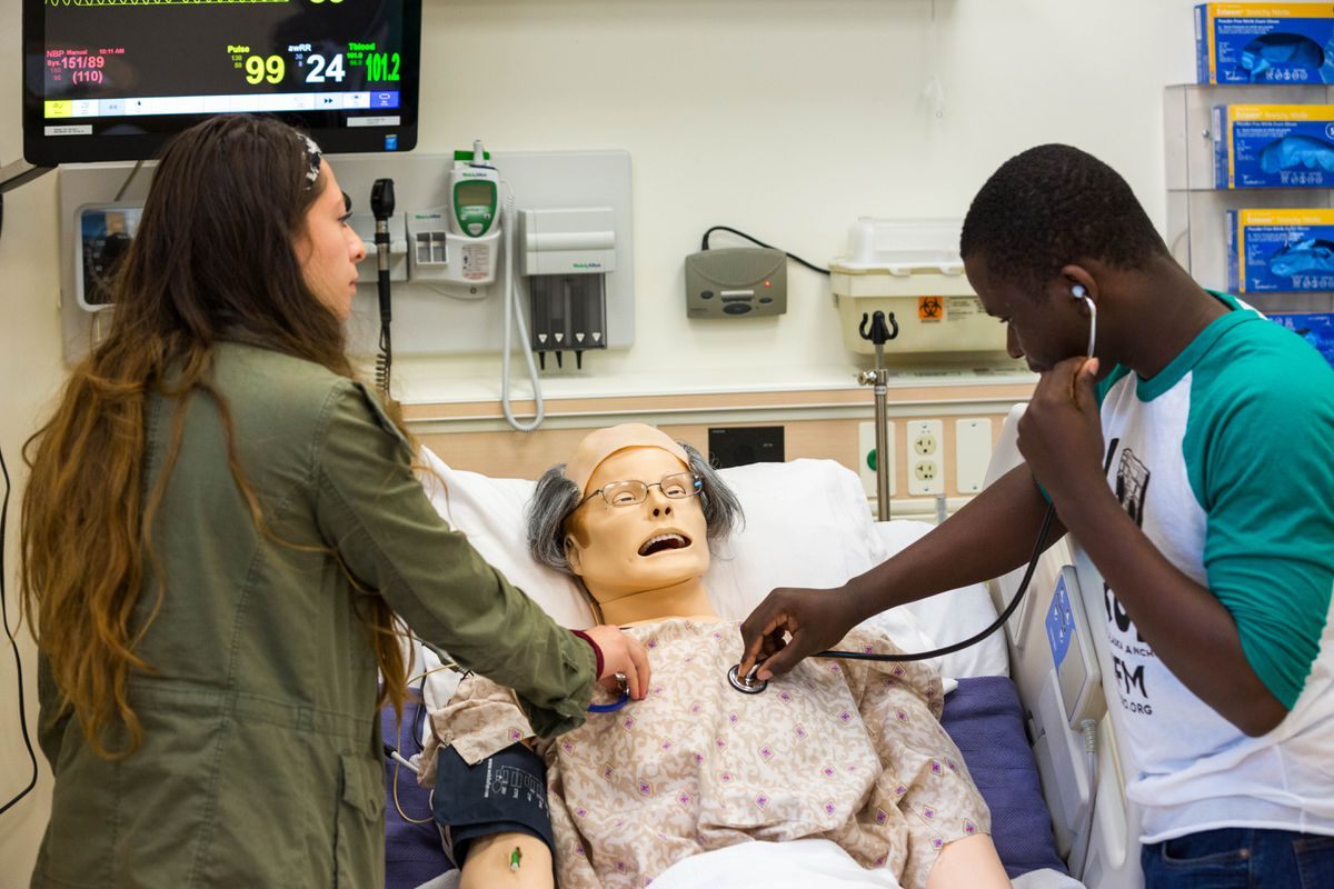 "Della Keats summer program students Sophia Thompson and Boazi Sefania evaluate a robotic ""patient"" at the University of Alaska Anchorage Health Sciences Building. The program encourages high school students to pursue careers in medicine. (Loren Holmes / Alaska Dispatch News)"