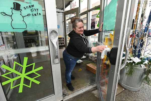Snow City Cafe server Selena Parten sanitized the entrance doors on Thursday, March 19, 2020. Parten said she was