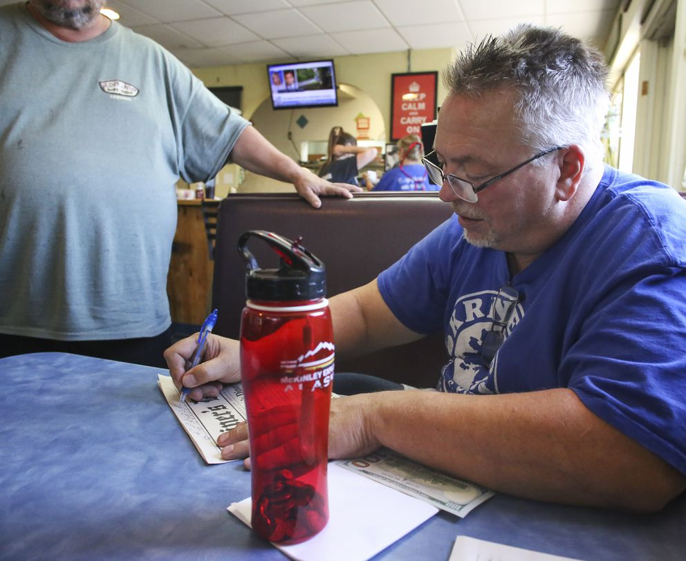 Andy Kriner signs a menu for a customer at Kriner's Diner in Anchorage on Aug. 4, 2020. (Emily Mesner / ADN)