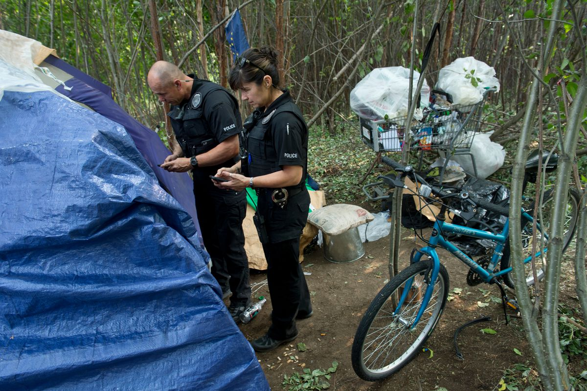Anchorage Police officers Gordon Korell, left, and Sally Jones speak with occupants of a tent at Cuddy Family Midtown Park on August 22, 2019, during the Point-In-Time count of homeless people in the city. (Marc Lester / ADN)