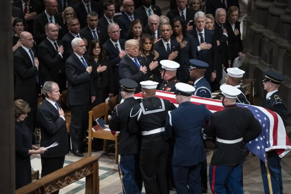 The flag-draped casket of former President George H.W. Bush is carried by a military honor guard past former President George W. Bush, President Donald Trump, first lady Melania Trump, former President Barack Obama, Michelle Obama, former President Bill Clinton, and former Secretary of State Hillary Clinton, at the conclusion of a State Funeral at the National Cathedral, Wednesday, Dec. 5, 2018, in Washington. In the second row are Vice President Mike Pence, and his wife Karen Pence, former Vice President Dan Quayle, and his wife Marilyn Quayle and former Vice President Dick Cheney. (AP Photo/Carolyn Kaster)